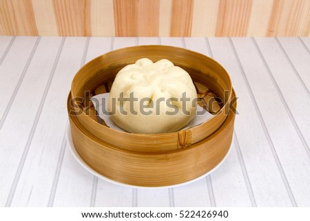 Steamed bun / Baozi/ Pao/ Bao inside Bamboo Steamer, Bakpao in Indonesia on Wooden Background