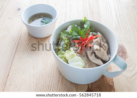 steamed chicken breast White cup on a plate placed on a wooden table