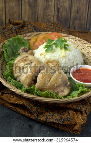 Steamed chicken served with rice, tomato and lettuce. Chicken firce is a famous food in South East Asia