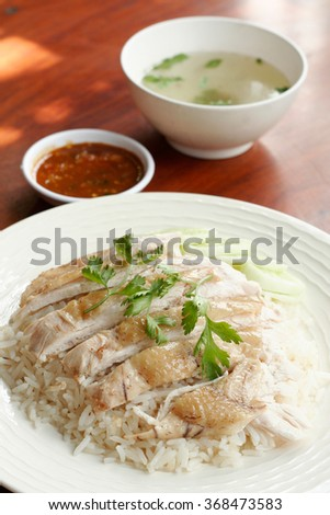 Steamed chicken with rice, soup, and spicy sauce.