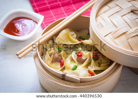 Steamed chinese dimsum on steamer with sweet and sour sauce