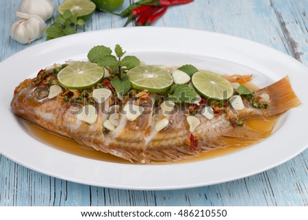 steamed fish with chili and lemon on blue wood table, thai food
