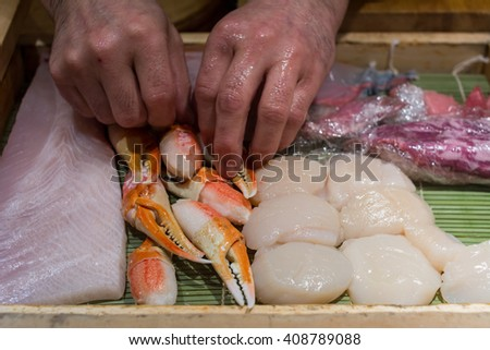Steamed giant crabs, shell, fish raw prepare to make sushi in Japanese food. Select focus at hand of chef - stock photo