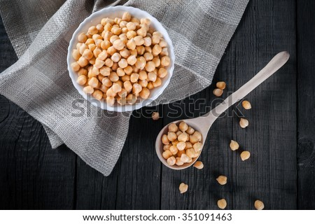 Steamed gold chickpeas in bowl on tablecloth with wooden spoon, tasty vegan food, top view