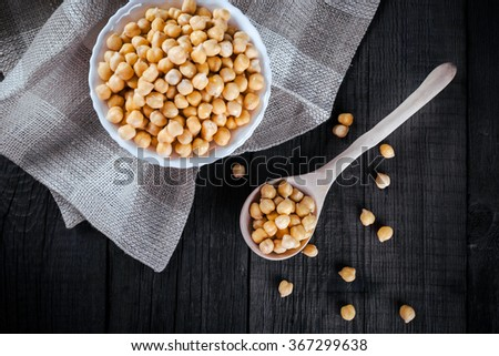 Steamed gold chickpeas in bowl on tablecloth with wooden spoon, tasty vegan food, top view - stock photo