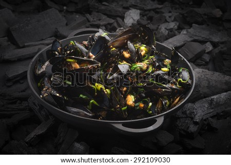 Steamed Mussels with vegetables in a black frying pan on the coals - stock photo