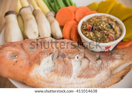 Steamed Nile tilapia  fish and vegetables, served with sauce on the wooden floor,Thai style food - stock photo