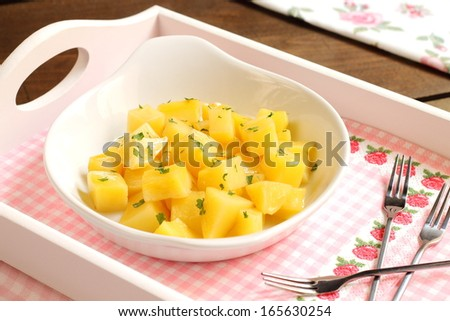 Steamed potato cubes with olive oil and parsley - stock photo
