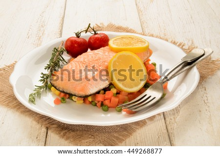 steamed salmon fillet on finely chopped vegetable, tomato and lemon on a plate