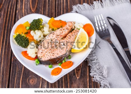 Steamed salmon with vegetables on  plate in the form of heart on wooden background - stock photo