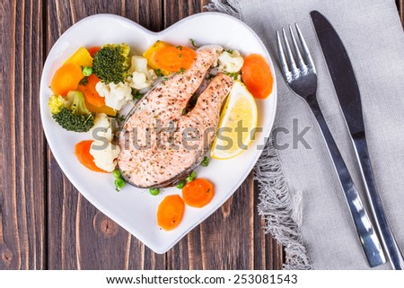 Steamed salmon with vegetables on  plate in the form of heart on wooden background