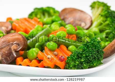 Steamed vegetables - carrots, broccoli, peas, green beans on a white plate