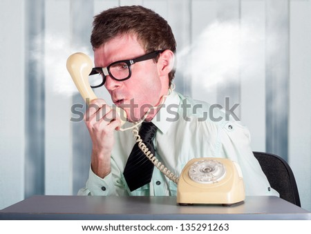 Steaming angry nerd businessman holding retro phone cord around big red head while shouting out demands to incompetent and unskilled workers in a staff management conceptual