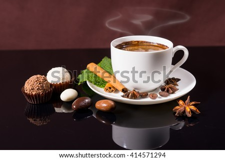 Steaming Black Coffee Served in White Cup and Saucer with Fresh Mint Sprig, Cinnamon Stick and Star Anise, on Shiny Black Reflective Surface with Chocolate Covered Coffee Beans and Truffles - stock photo