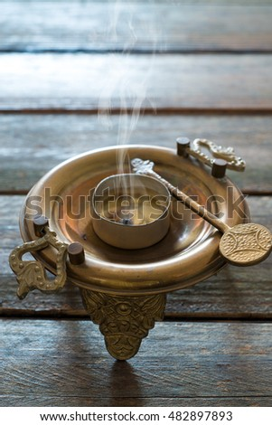 steaming bronze brazier over wooden table