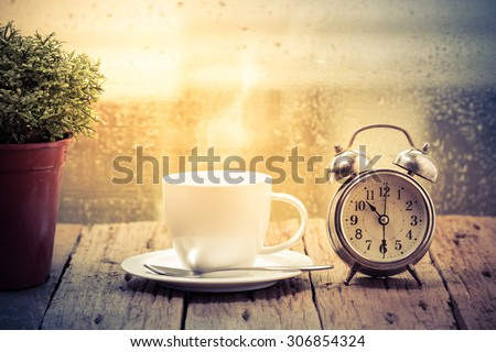 Steaming coffee cup on a rainy day window background,good time of coffee - stock photo