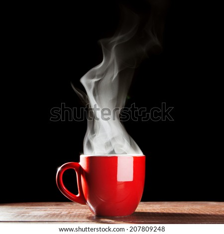 Steaming coffee cup on dark background - stock photo