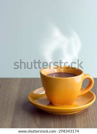 steaming coffee cup on table - stock photo