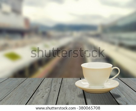 Steaming coffee cup on window background. A view of The train tracks.