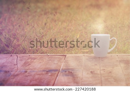 Steaming coffee cup on wood table. grass background - stock photo