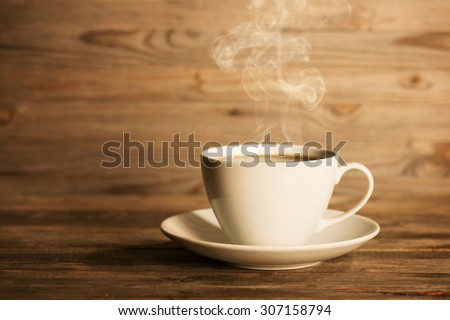 Steaming coffee in white mug and saucer in soft focus setting with dramatic ambient light, over dark wooden background. - stock photo