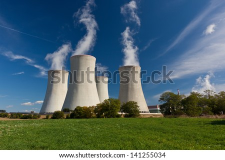 Steaming cooling towers on green meadow