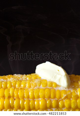 Steaming corn with melting butter and salt close up on a black.