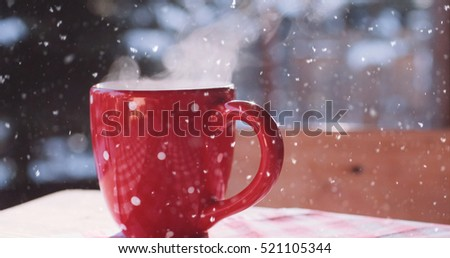 Steaming Cup of Hot Coffee or Tea standing on the Outdoor Table in Snowy Winter Morning under snowfall. Cozy Festive Red Mug with a Warm Drink in Winter Garden. Christmas Morning Concept