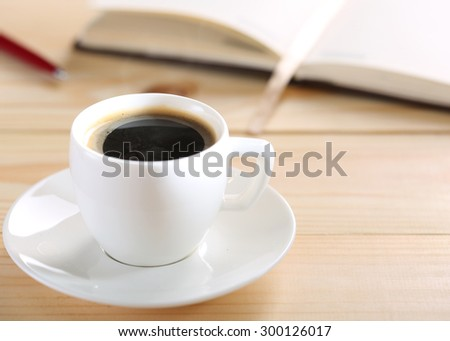 Steaming hot morning cup of coffee on wooden table, notepad or book and pen closeup. Little lunch break during working day. Business or education pause concept. Coffee house or restaurant table