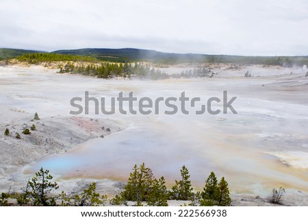 Steaming lake and colorful thermophilic organisms in the streams of hot water.  Norris Geyser Basin, Yellowstone National Park USA - stock photo