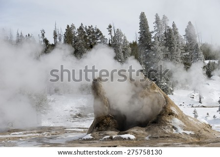 Steaming pipe of a geyser in winter. Yellowstone National Park. - stock photo
