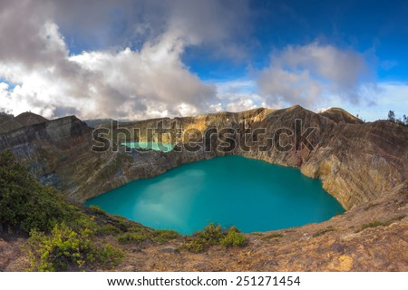 Steaming volcanic colorful lakes in Kelimutu craters on a bright sunny day - stock photo