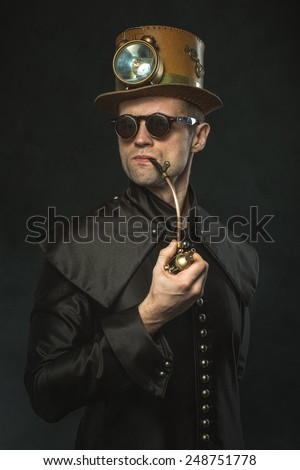 Steampunk man in a hat smoking a pipe - stock photo