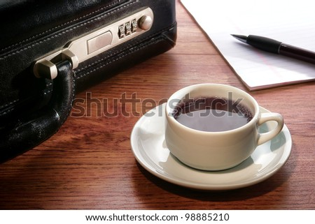 Steamy hot cup of black coffee with warm steam and pen on paper notepad with businessman briefcase on an office conference table desk during a business meeting break at work - stock photo