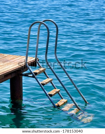 Steel and wooden old ladder pier on the sea