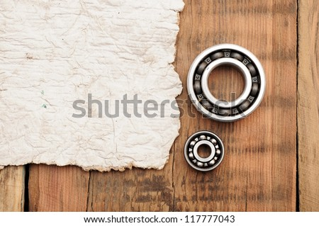 steel ball bearings with old paper on wooden table. space for your text