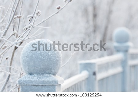 Steel balls of iron fence in a snowy frost - stock photo