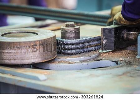 Steel bar bending machine work. - stock photo