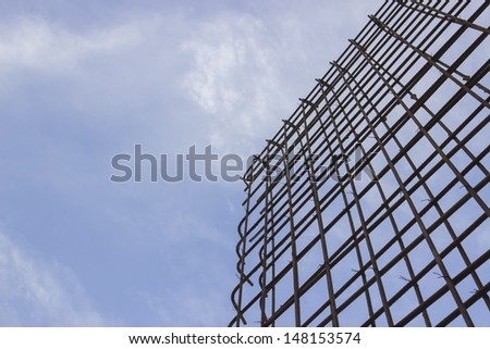 steel bars construction at construction site, against blue sky. background with a divided space for text or image