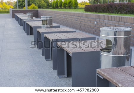 Steel bin and brown wooden benches in a recreation area. - Stock image