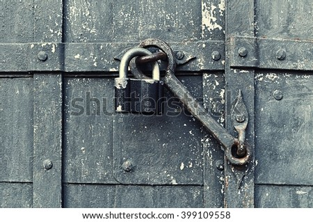 Steel black padlock hanging with old door heck at the iron forged old door. Selective focus at the padlock and door heck. Textured architectural background - stock photo