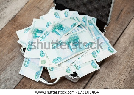 Steel case with Russian banknotes inside on wooden floor - stock photo