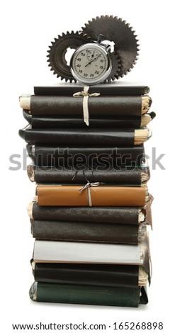 Steel cogwheels, stopwatch on stack of old paper folders - stock photo