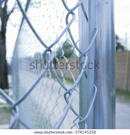 Steel corner post and links of a residential chain link fence, running down the edge of a road.  Focus point is the post and links.  Rule of thirds crop. - stock photo