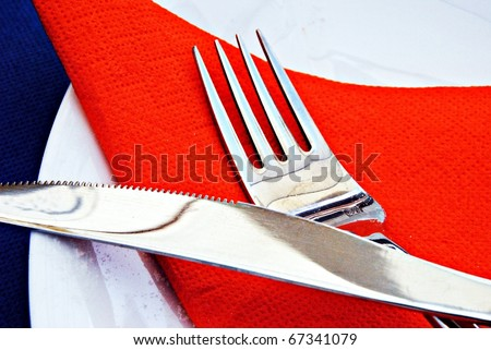 Steel cutlery on red napkin