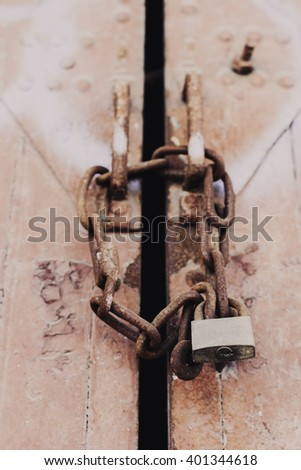 Steel door of a long forgotten warehouse - chained with a rusty chain and an old padlock - stock photo