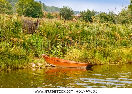 steel fishing rowboat tied to a red wooden gate