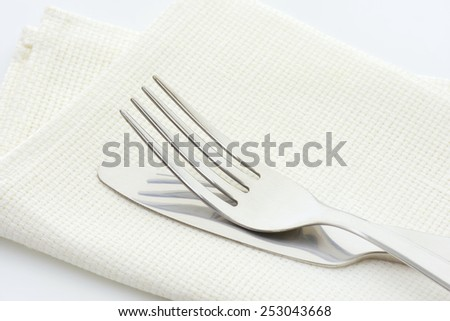 Steel fork and knife in a linen serviette on white background - stock photo