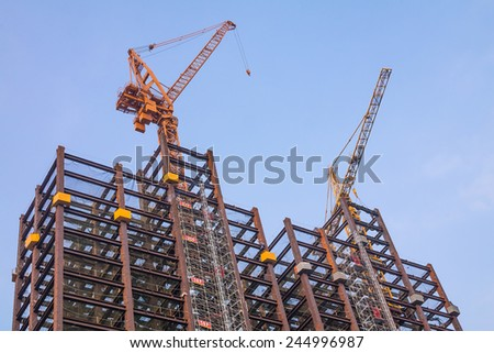 steel frames of a building under construction with 2 tower cranes on top