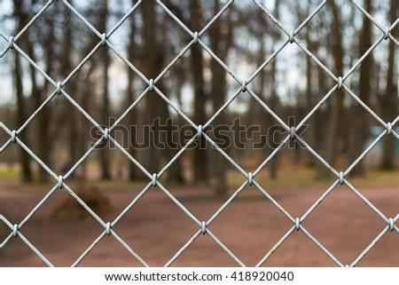 Steel Grating grid on blur park background.  - stock photo